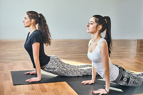 Two young women doing yoga asana cobra pose. Bhujangasana