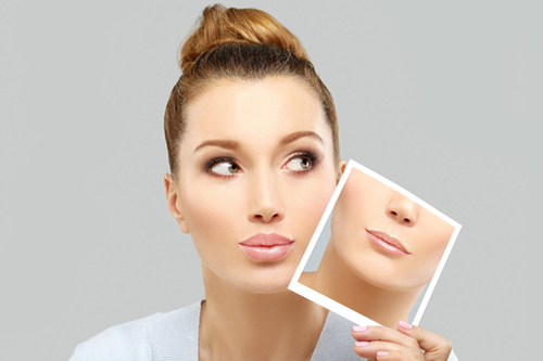 唇の写真を持つ女性
