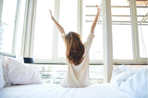 目覚めの良い朝女性が両腕を伸ばす