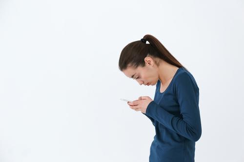 猫背でスマートフォンを見ている女性
